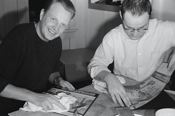"Chris Strachwitz and Wayne Pope pasting their first album covers for ""Texas Songster""  1960 Photograph: Alice Pope Courtesy of Chris Strachwitz and/or the Arhoolie Foundation R2018.1101.260"