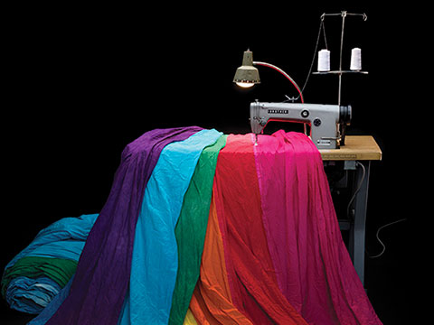 Rainbow flag created by Gilbert Baker for the ABC television miniseries When We Rise with sewing machine and table used by Gilbert Baker in its production. Courtesy of Tom Taylor
