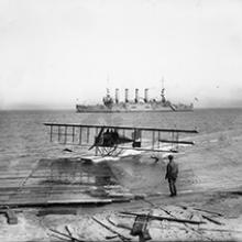Loughead Brothers' Alco Hydro-Aeroplane Model G beaching with the cruiser USS Milwaukee offshore, San Francisco Bay  1915