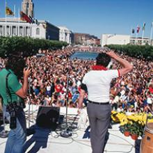 Supervisor Harvey Milk addressing Gay Freedom Day celebrants gathered at United Nations Plaza in San Francisco, with the first rainbow flags visible in the distance  June 25, 1978