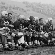 49ers bench during a game at Kezar Stadium; team physician, Frankie Albert (63), Gordy Soltau (51), Jim Powers (62), Alyn Beals (53), Verl Lillywhite (71), and Leo Nomellini (42)