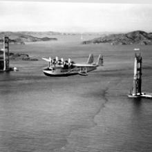 Sikorsky S-42 airplane flying over the Golden Gate Bridge before completion