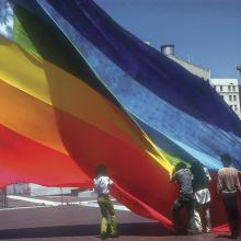 Gilbert Baker (in vest) and colleagues raising one of the first rainbow flags at United Nations Plaza in San Francisco