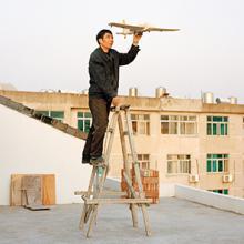 Yuan Xiangqiu holds a model airplane his son made in Tiantai, Zhejiang Province 2015