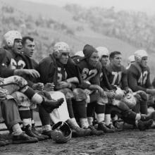 49ers bench during a game at Kezar Stadium; Frankie Albert (63), Gordy Soltau (51), Jim Powers (62), Alyn Beals (53), Verl Lillywhite (71), and Leo Nomellini (42)1950