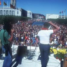 Supervisor Harvey Milk addressing Gay Freedom Day celebrants gathered at United Nations Plaza in San Francisco, with first rainbow flags visible in the distance