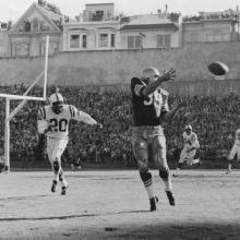 Halfback Hugh McElhenny receives a pass during a 17-13 victory over the Baltimore Colts before a crowd of 59,950 at Kezar Stadium and hundreds more crowding nearby rooftops