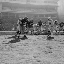 Running back Joe Perry rushes behind guards Lou Palatella (68) and Bruce Bosley (77) during a 17-13 victory over the Baltimore Colts at Kezar Stadium