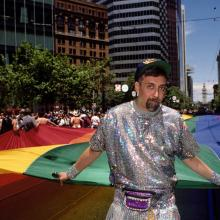 Gilbert Baker with portion of the mile-long rainbow flag on Market Street during the LGBT Pride Celebration in San Francisco