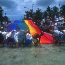 "LGBTQ activist and labor organizer Cleve Jones (with hand raised) and colleagues with the 1.25 mile-long ""Sea-to-Sea"" flag created by Gilbert Baker and a team of volunteers. The flag was produced for the 25th Anniversary of the rainbow flag and unfurled from the Gulf of Mexico to the Atlantic Ocean on Duval Street in Key West, Florida"