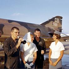 Flight attendant Mary Jo Hunt (left) and Pan American World Airways crew with fighter pilots, Da Nang Air Base, Vietnam  c. 1968