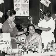 Hair demonstration in the Madam C. J. Walker booth at the Regional Beauty College Convention; Walker's attorney F. B. Ransom, who played a significant role in her business and personal life, is pictured on the left