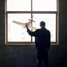 """Yuan Xiangqiu gazes out the window of his home in Tiantai, Zhejiang province. The 65-year-old said he was inspired to build a plane the first time he saw one on television. """"I can teach myself to be a carpenter, and I can make a rice thresher, so I can surely build an airplane too,"""" he remembers thinking 2015"""