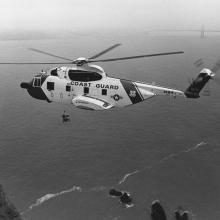 Sikorsky HH-3F Pelican helicopter hovers over Lands End with Golden Gate Bridge in background  1989